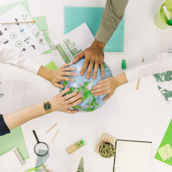 group-businesspeople-placing-their-hands-globe_23-2147826545